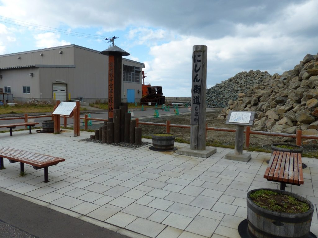 左側が「官軍上陸の地」碑。右側は「にしん街道」の標柱。